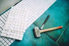 工业家庭建筑-锤子和马赛克,白色大理石石陶瓷砖 免版税库存照片
