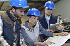 工业工程师见面和谈论在机械工厂 免版税库存照片