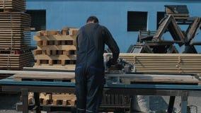 工业年轻木匠工作者背面图特别制服的使用木切割机 股票录像