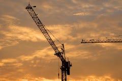 工业建筑用起重机和大厦剪影在日出 库存图片