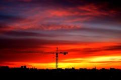 工业建筑用起重机和大厦剪影在sunse 免版税库存图片