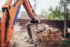 工业拆毁老房子和废墟的反向铲挖掘机和推土机 库存照片