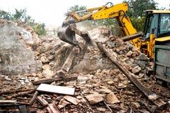 工业挖掘机和推土机装货爆破混凝土墙 免版税库存照片