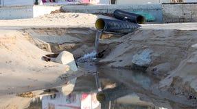工业污水,管道释放液体工业废料入城市海滩的海 从a的肮脏的污水流程 免版税库存图片
