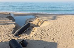 工业污水,管道释放液体工业废料入城市海滩的海 从a的肮脏的污水流程 库存图片