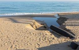 工业污水,管道释放液体工业废料入城市海滩的海 从a的肮脏的污水流程 免版税图库摄影