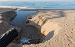 工业污水,管道释放液体工业废料入城市海滩的海 从a的肮脏的污水流程 免版税库存照片