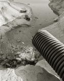 工业污水,管道释放液体工业废料入城市海滩的海 从a的肮脏的污水流程 库存照片