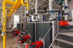 工业燃气锅炉房子内部有许多管子和煮沸的 免版税库存照片