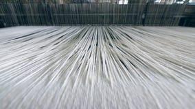 工业纺织品工厂 关闭移动通过织布机的厚实的白色螺纹 股票录像