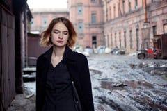 工业风景背景的哀伤的红发女孩  走的妇女 库存照片
