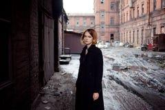 工业风景背景的哀伤的红发女孩  走的妇女 免版税库存照片
