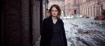 工业风景背景的哀伤的红发女孩  走的妇女 免版税库存图片