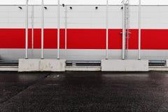 工业,都市背景 红色和灰色金属墙壁和空的停车场 免版税库存照片