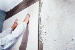 工业细节,安装大陶瓷砖的杂物工在卫生间墙壁 淋浴在陶瓷砖包括的区域与强的adhes 库存照片