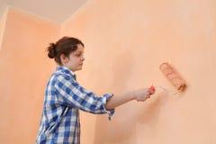 年轻工人油漆墙壁在桔子的一间屋子里 免版税库存图片