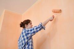 年轻工人油漆墙壁在桔子的一间屋子里 免版税库存照片