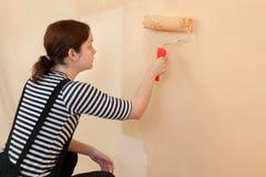 年轻工人油漆墙壁在桔子的一间屋子里 免版税图库摄影