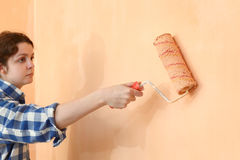 年轻工人油漆墙壁在桔子的一间屋子里 库存照片