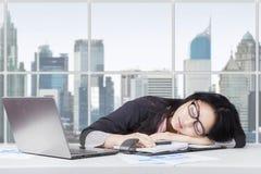 年轻工人看起来疲乏和睡觉在办公室 免版税图库摄影