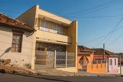 工人阶级在圣曼努埃尔上色了房子和篱芭在一条空的街道在一个晴天 免版税库存照片