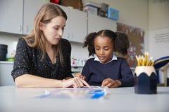 工作一在一个的年轻女性主要学校老师与女小学生在一张桌上在教室,关闭 免版税库存图片