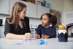 工作一在一个的年轻女性主要学校老师与女小学生在一张桌上在教室,看彼此,接近的u 库存照片
