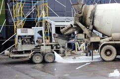 工作一起倾吐的水泥地板的混凝土泵和搅拌器在购物中心修理 库存照片
