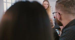 工作与不同种族的年轻雇员一起的成功的欧洲女实业家在办公室在桌后的队会议上 影视素材