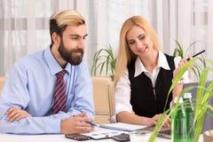 工作与俏丽的女实业家的商人在办公室 免版税库存照片