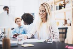 工作与同事一起的美丽的白肤金发的妇女在办公室 谈论小组四个的工友企业项目 水平 免版税图库摄影