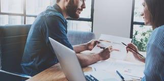 工作与商务伙伴的西班牙年轻商人在晴朗的办公室 被弄脏的背景 水平 播种 免版税库存照片