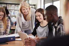 工作与大学生的女老师在图书馆里 免版税库存图片