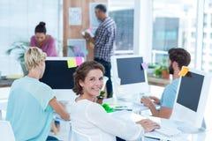 工作与她的同事的微笑的少妇在书桌 免版税库存图片