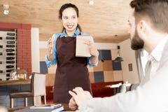 工作与客户的正面西班牙女服务员 免版税库存图片