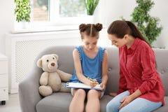 工作与小孩的年轻女性心理学家 免版税库存图片