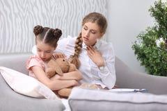 工作与小孩的年轻女性心理学家 免版税库存照片