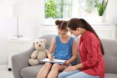 工作与小孩的年轻女性心理学家 免版税图库摄影