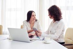 工作与小配件一起的两名妇女在办公室 免版税图库摄影