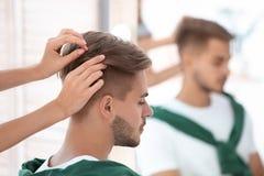 工作与年轻人的专业美发师 库存照片