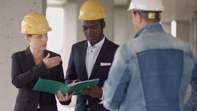 工作与建筑师工程师的商人在有图纸的楼房建筑站点检查计划 免版税图库摄影