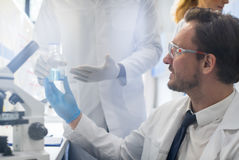 工作与显微镜、队在实验室做研究,男人和妇女的男性科学家做科学实验 库存照片