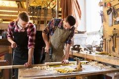 工作与木板的木匠在车间 免版税库存图片