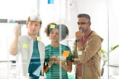 工作与玻璃委员会的创造性的队在办公室 免版税库存图片
