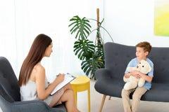 工作与男孩的儿童心理学家在办公室 图库摄影
