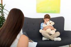 工作与男孩的儿童心理学家在办公室 免版税库存照片
