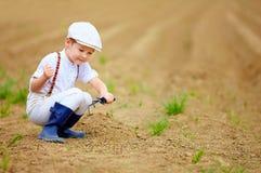 工作与的逗人喜爱的矮小的农夫在春天领域用小锄头 免版税库存图片