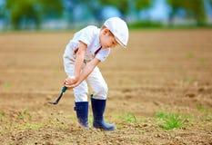 工作与的逗人喜爱的矮小的农夫在春天领域用小锄头 库存照片