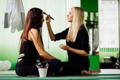 工作与美丽的少妇的专业化妆师 健身模型,航空瑜伽 坐在莲花坐 库存照片