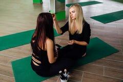 工作与美丽的少妇的专业化妆师 健身模型,航空瑜伽 坐在莲花坐 免版税库存图片